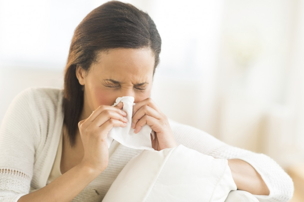 Woman Blowing Nose With Tissue At Home