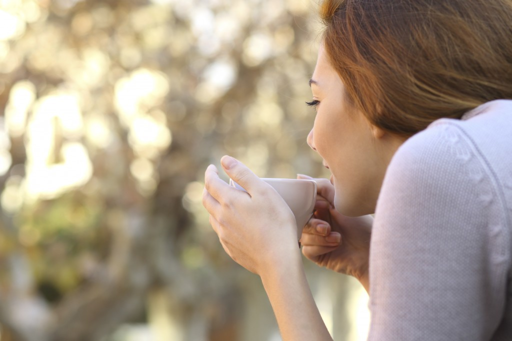 Relaxed woman holding a cup of coffee outdoor
