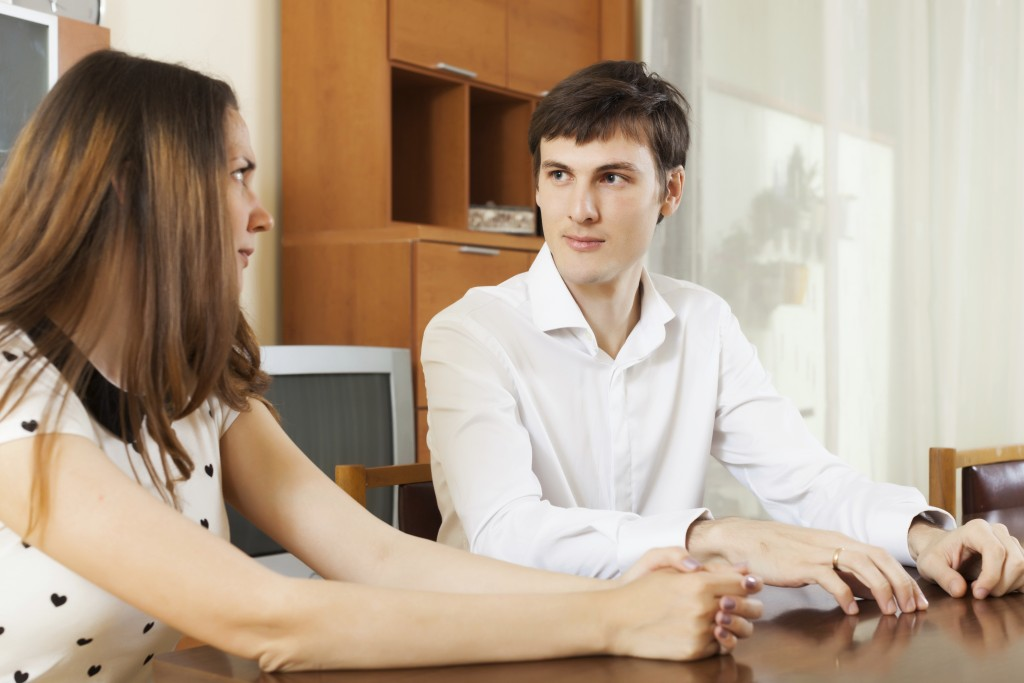 Serious young couple talking in home
