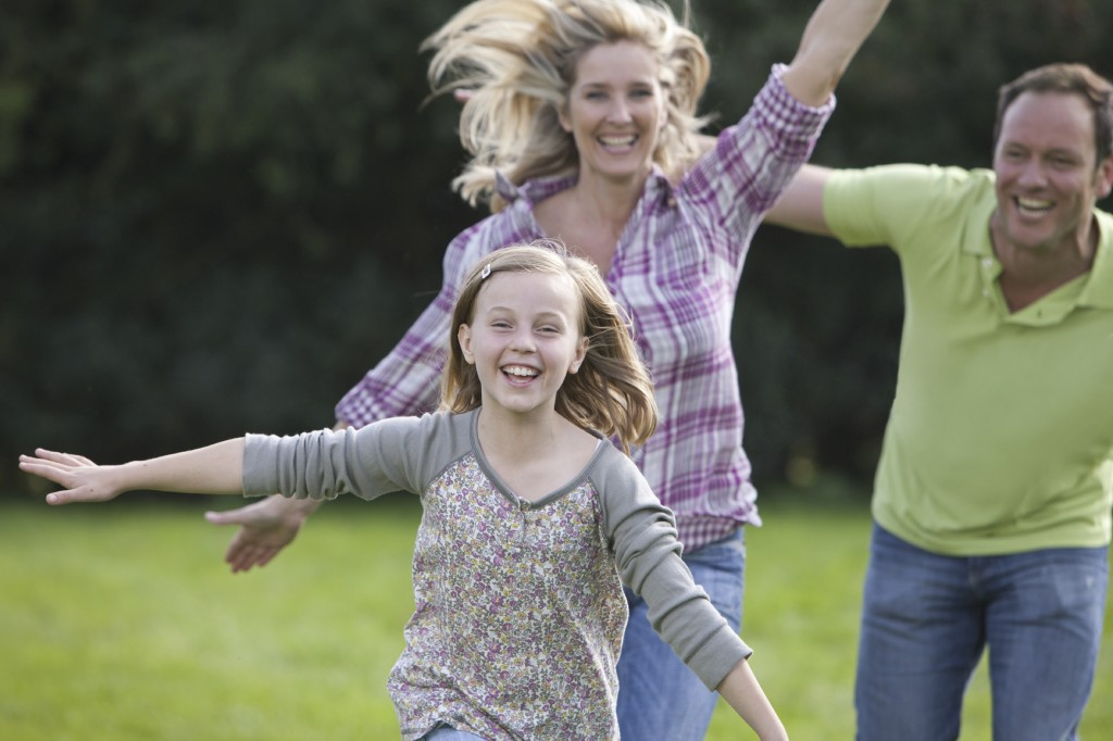 Happy family with arms outstretched running in field