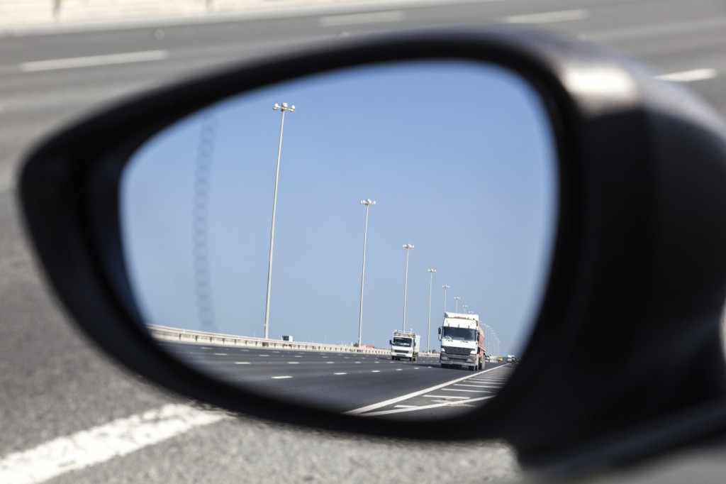 Trucks on highway in the rear-view mirror