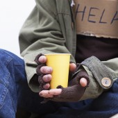 Hands of homeless with a paper cup