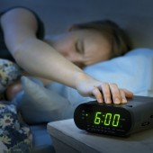 Woman waking up early with alarm clock
