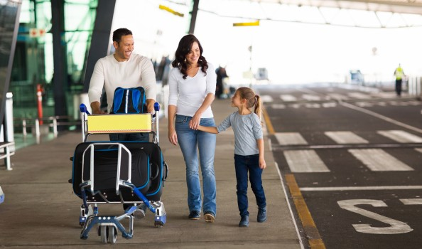 young family at airport with a trolley full of luggage