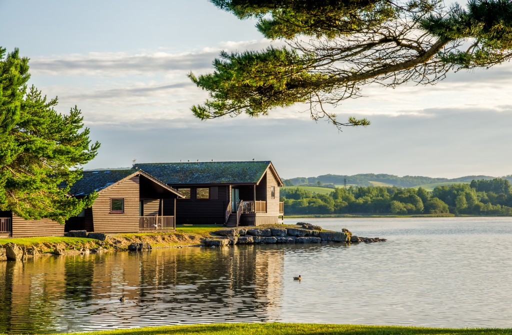 A peaceful scene of wooden holiday lodges beside a still lake