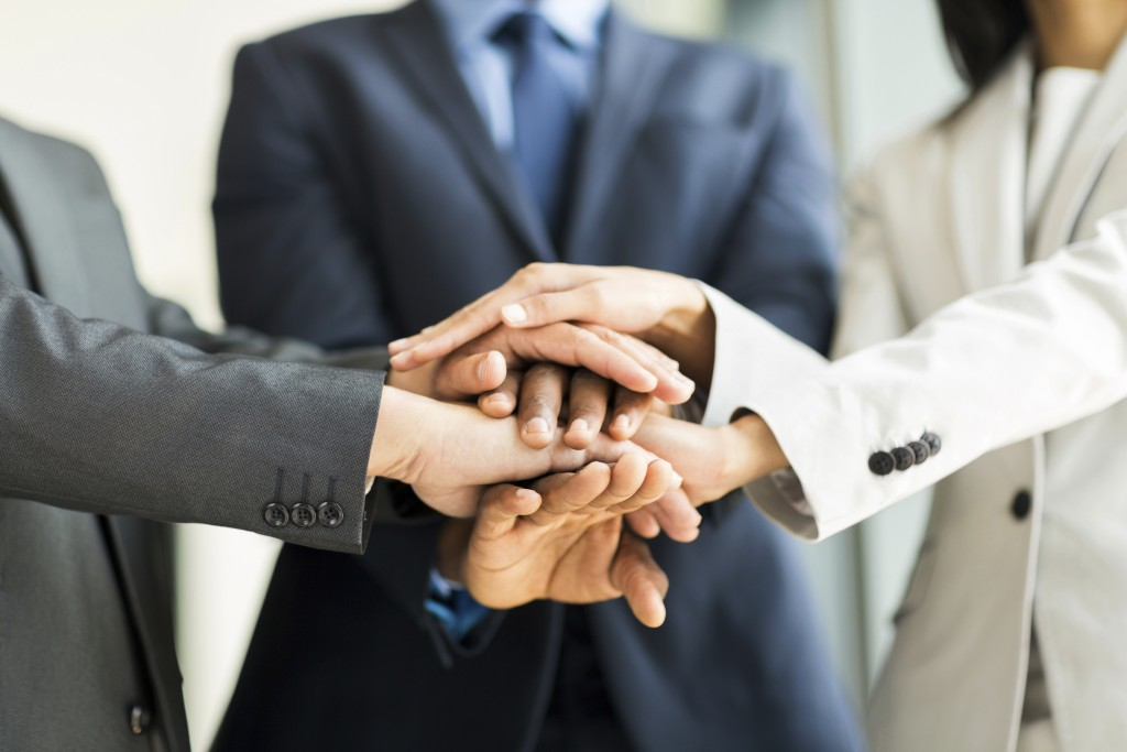 multiracial business people putting their hands together