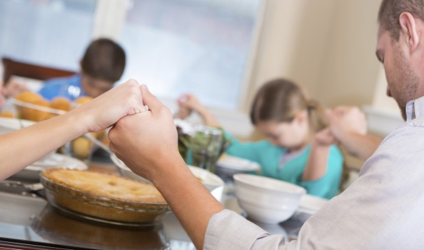 Family joining hands to pray over meal at dinner table