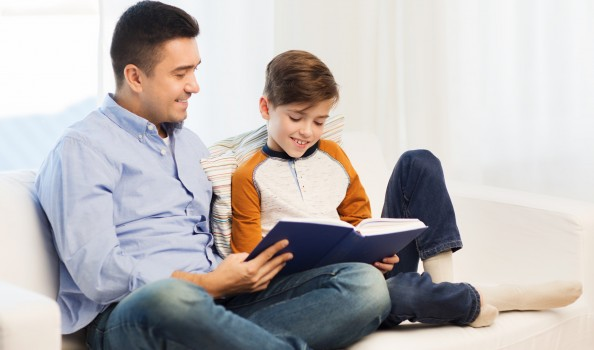 happy father and son reading book at home