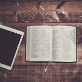 Bible with tablet and coffee in a wooded table.