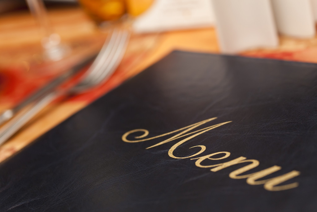 Menu on a restaurant table next to knife and fork