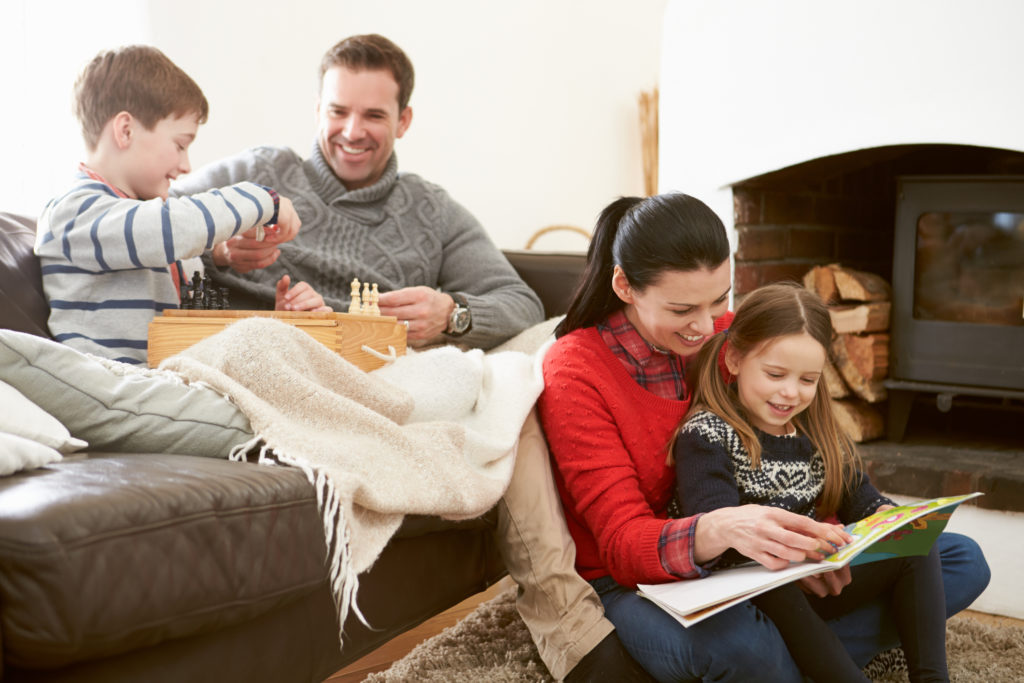 Family Relaxing Indoors Playing Chess And Reading Book