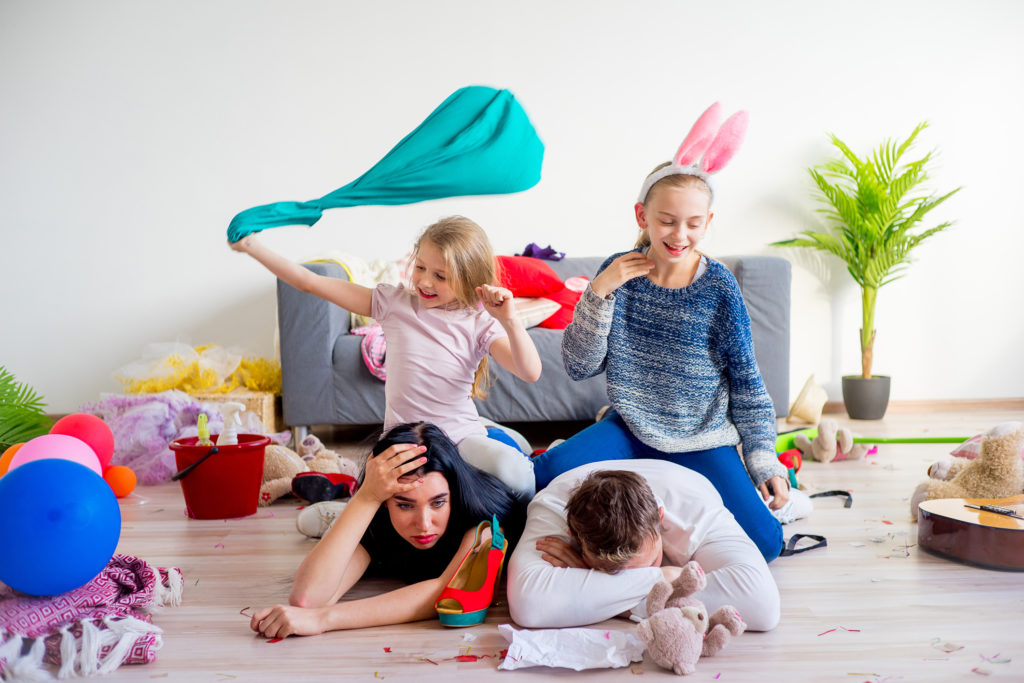 exhausted parents lieing on the floor while their kids have boundless energy