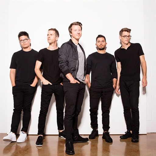 5 guys in black clothing with a white background.