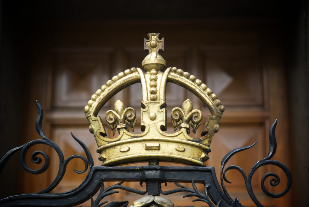 A decorative, gilded crown on a wrought iron fence outside London's National Portrait Gallery with a wood panel door in the background.