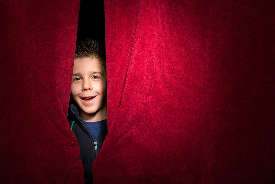 smiling boy peeking out behind a stage curtain