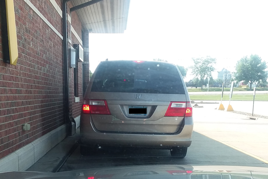 a tan minivan in the McDonalds drive-thru