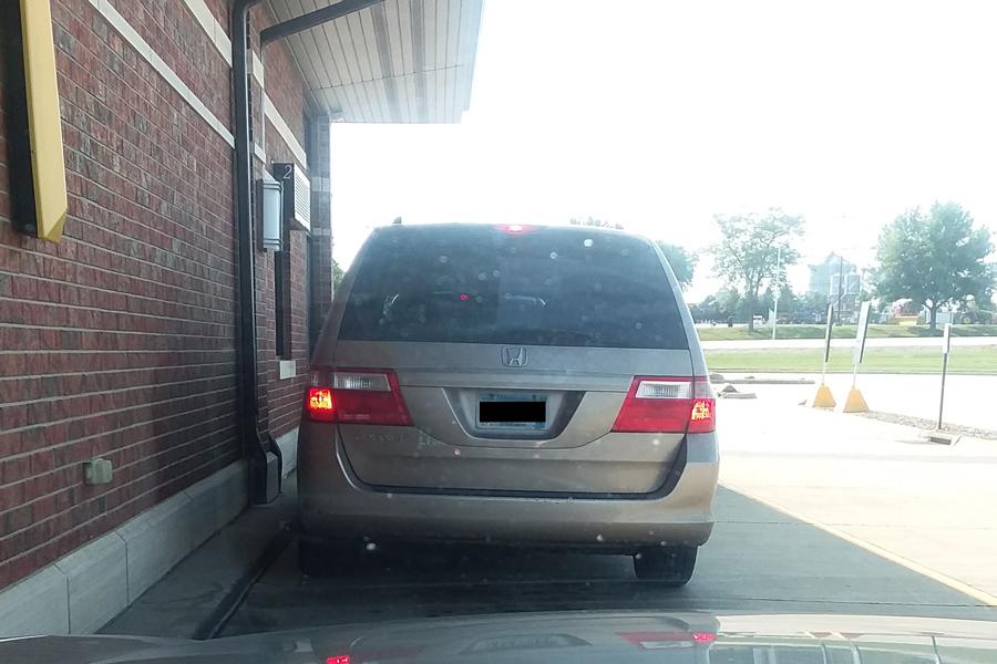 a tan minivan in the McDonalds drive-thru