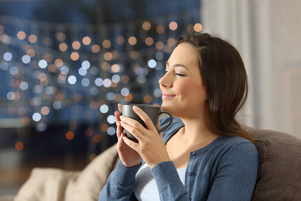 Woman relaxing drinking coffee in the night at home