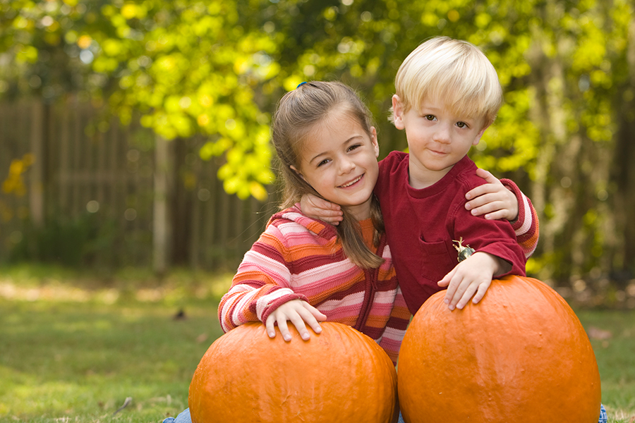 a smiling boy and girl behind two large pumpkins
