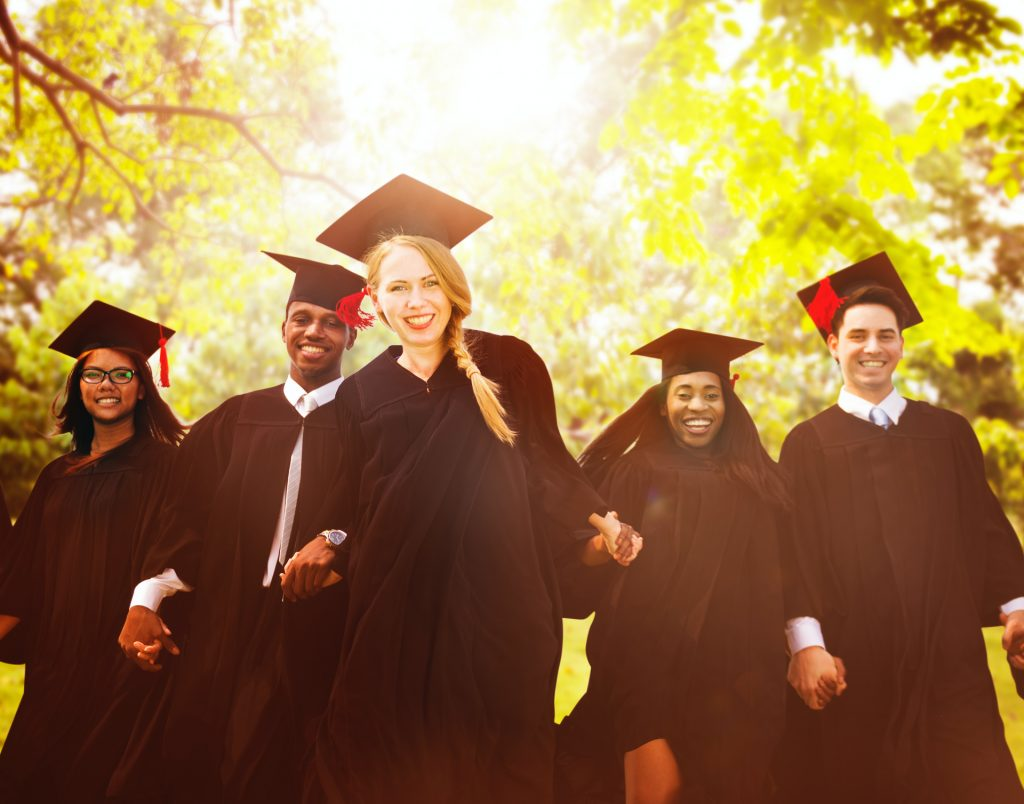 Graduates in caps and gowns holding hands