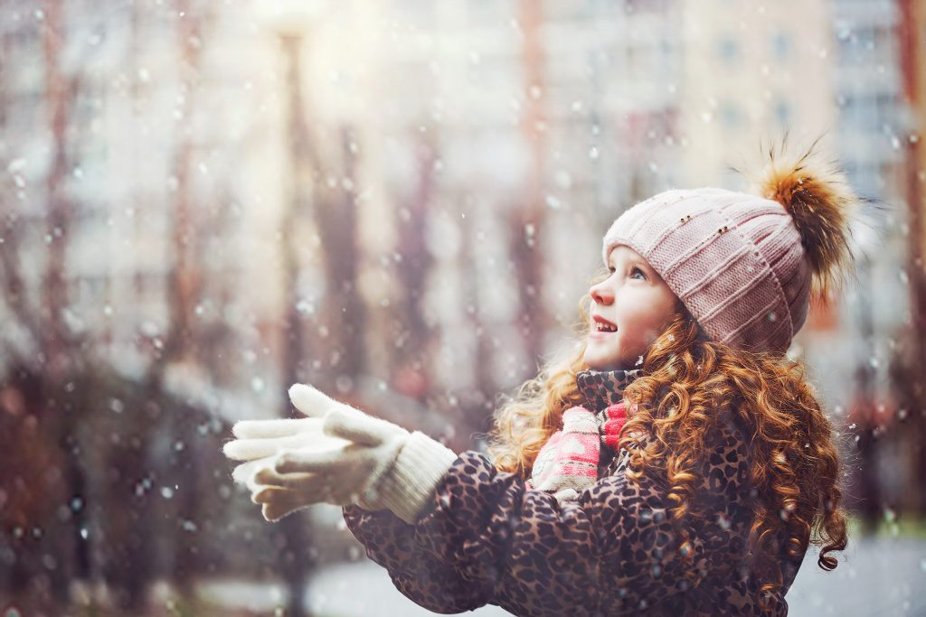 Little girl stretches her hand to catch falling snowflakes.