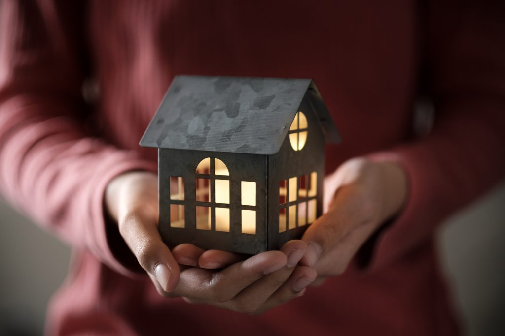 Miniature house model with illuminated light in the hand
